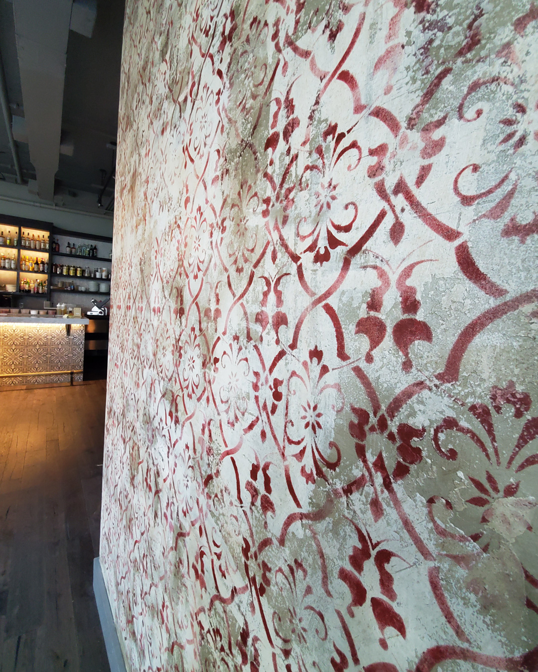 "Sylvia T Designs – An attention-grabbing feature wall in Claret, a wine bar in the Lower Garden District of New Orleans. It's unique combination of stencil work and plaster where we utilized a ""pulling-off"" technique to give it an aged look."