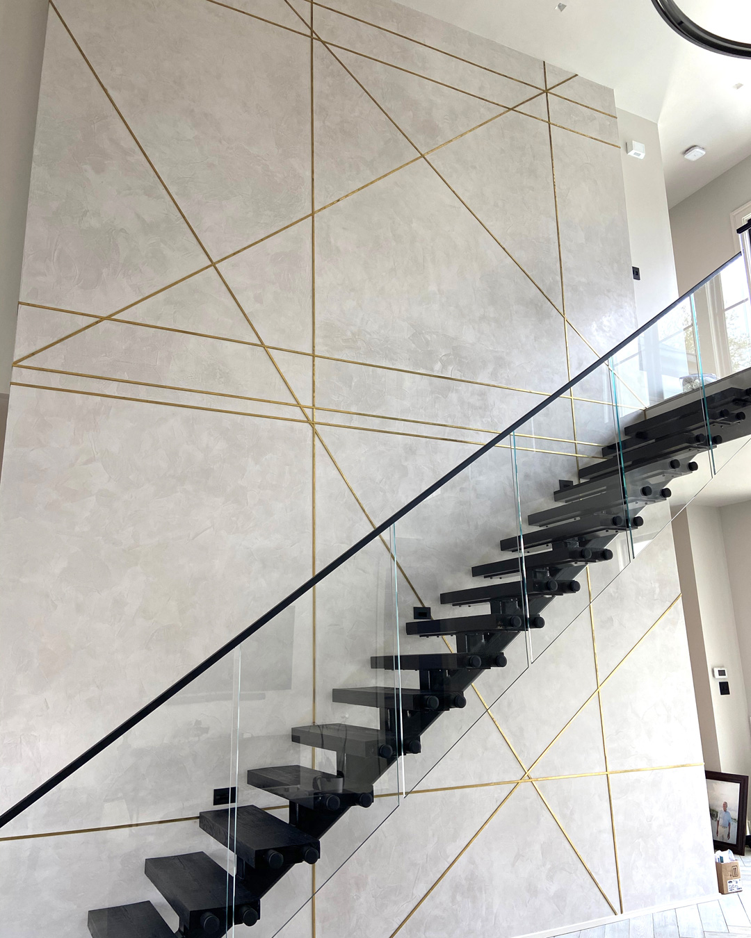 Sylvia T Designs – A new construction, residential project in the Lakeview neighborhood of New Orleans. This stunning feature wall in the living area boasts a beautiful gloss plaster finish and metal inlays. It's a showstopper!